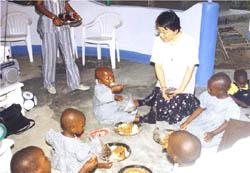 孤児たちの食事のお世話をするシスター中村