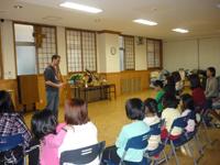 六本木チャペルセンターに避難していた福島の家族と子供達家族を励まそうと尺八演奏を披露しているアレック・リメイさん(上智大学語学講師)